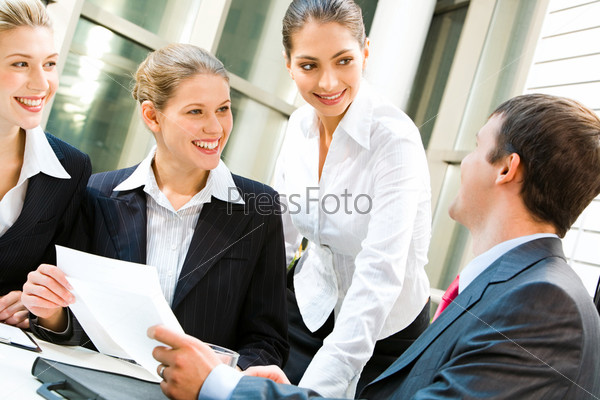Image of three women looking at business man in an office