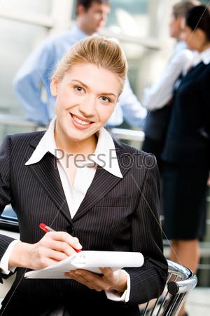 Деловая женщина, пишущая что-то в блокноте с улыбкой