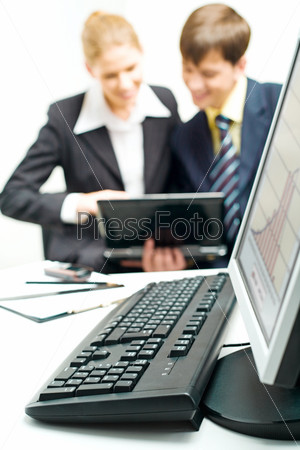 Computer placed on a table on the background of business people