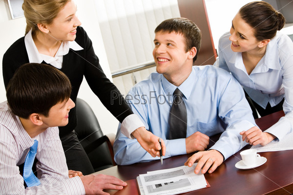 Four smiling business people discussing an affair