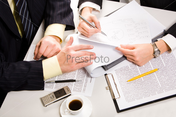 Horizontal image of two business people's hands lying on the table with a cup of coffee and a cell near by