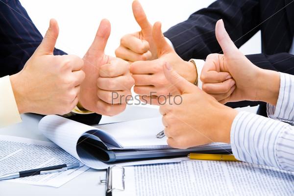 Трое людей поднимают большие пальцы в знак замечательного бизнес плана