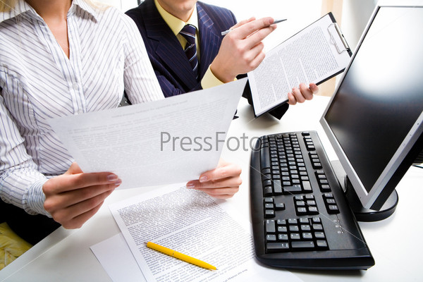 A business lady and a businessman reading and discussing a business contract