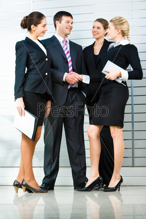 Image of four business people standing with handshaking of the business lady and her business partner at the front