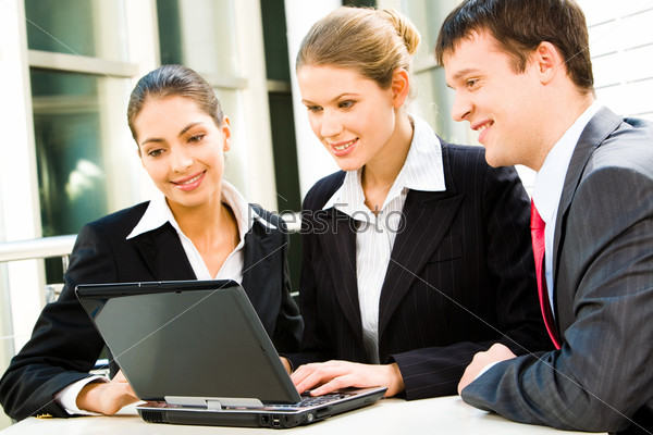 Group of three business people sitting and looking into the screen of the laptop smiling