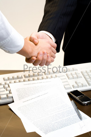 Two business people shaking hands on the background of the keyboard and the signed contract