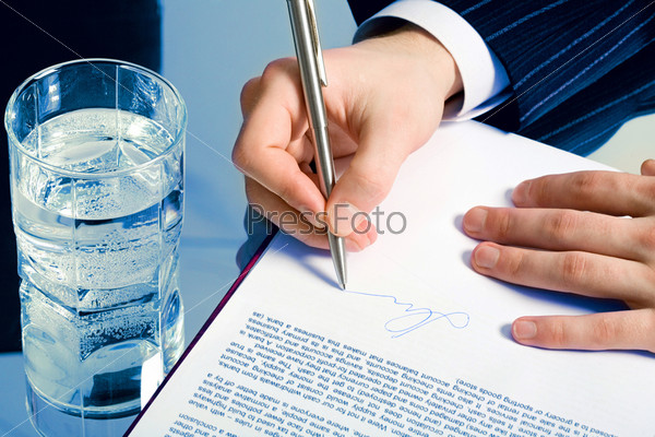 Horizontal photo of a businessman's hands signing a contract with a glass of water on the backgrounds