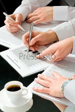 Image of business people's hands during discussion of business documents with a cup of coffee near by