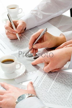 Close-up of teamwork: business people's hands pointing at the paperwork