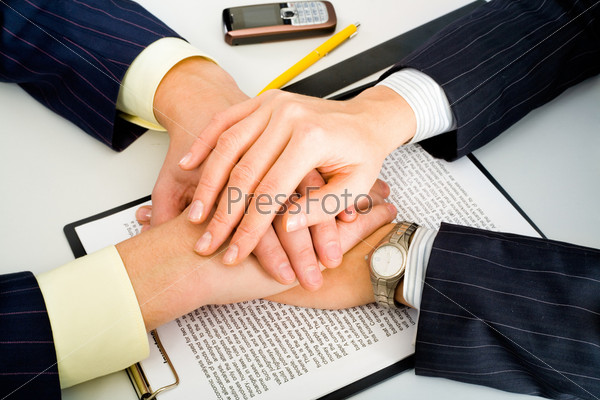 Photo of two business partners holding their hands over the contract lying on the table with a yellow pen, a ruler and a cellular phone near by