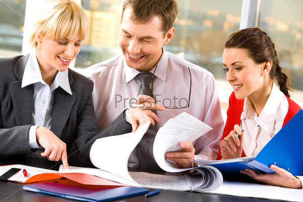 Two business ladies and a businessman looking through their business documents and discussing them smiling
