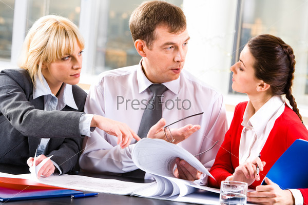 Image of a business lady looking attentively at the speaking business leader while the other woman pointing at some details in the document