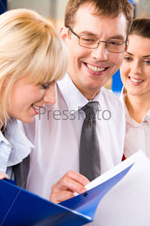 Image of two business ladies and a businessman reading and discussing business plans happily smiling