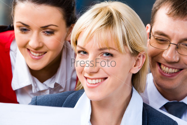 Photo of three smiling business people's faces with a blonde young successful business lady at the front