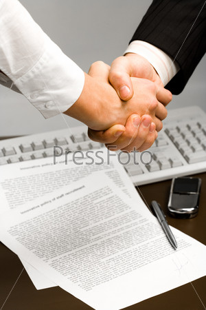 Image of human hands holding each other over paper, keyboard, pen, phone in the background