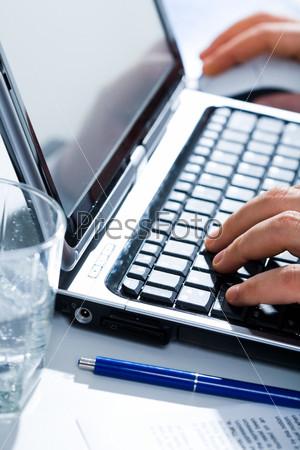 Руки человека, нажимающего на кнопки клавиатуры с рядом находящимися ручкой и стаканом воды