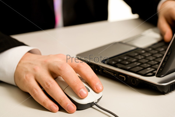 Human hands touching computer mouse and keys of opened laptop