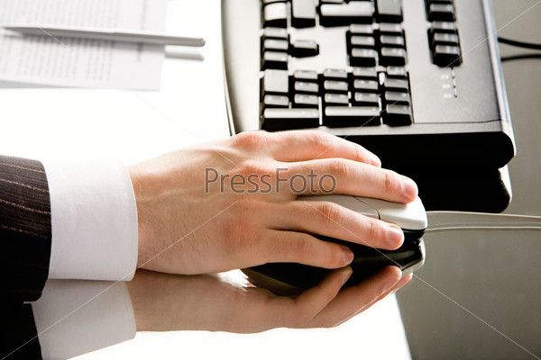 Image of hand with computer mouse placed on a working table