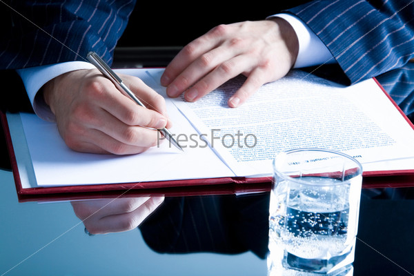 Image of human hand holding a pen over paperwork