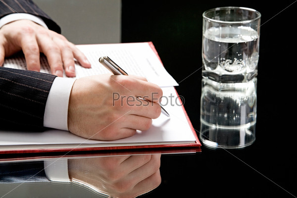 View of human hands on with a pen ready to write with a glass of water standing near by