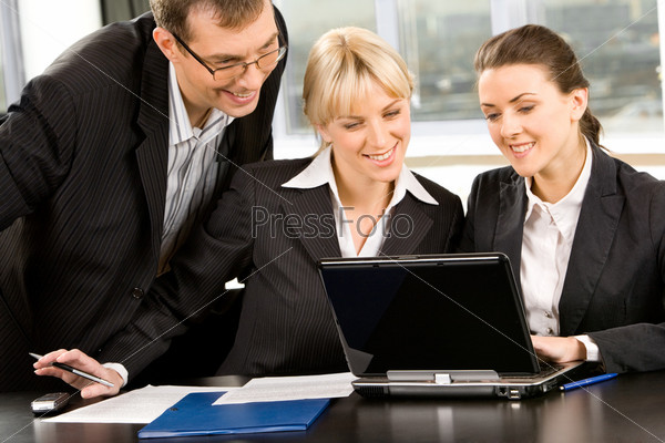 Group of three business people looking at monitor of a laptop