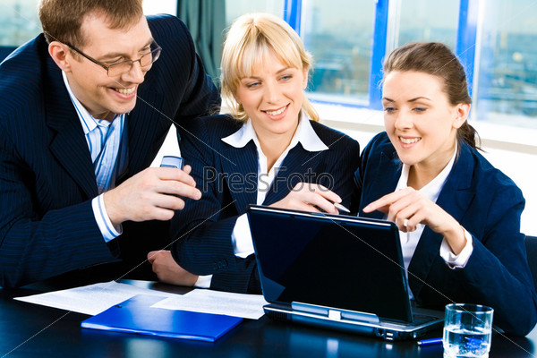 Team of three confident people gathered together for discussing a business-plan
