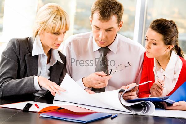 Команда из трех деловых людей, сидящих за столом с документами и обсуждающих важные вопросы