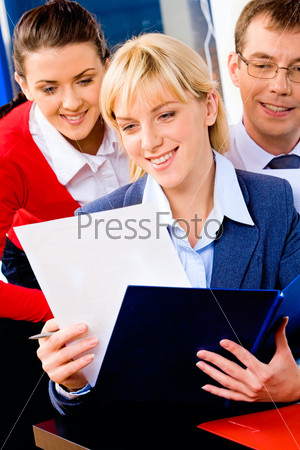 Успешный предприниматель, читающая бизнес-план на фоне деловых людей