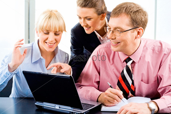 Business woman is explaining the correct way of analysis to his colleagues pointing at the monitor of laptop