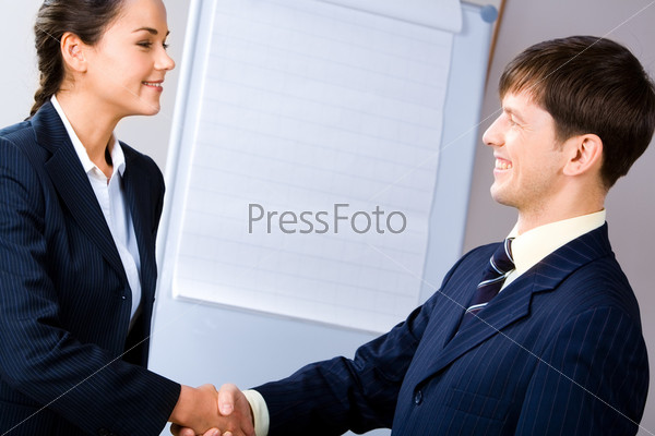 Business people shaking hands making an agreement on the background of whiteboard