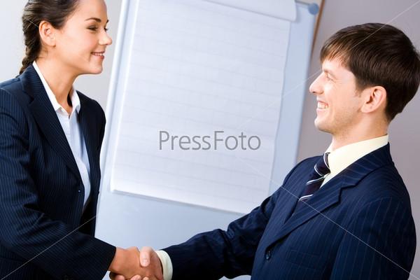 Деловые люди пожимают руки друг другу при заключении соглашения на фоне доски