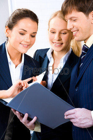 Team of three people discussing an important document at business meeting