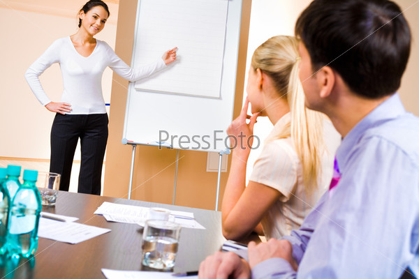 Businesswoman doing presentation on whiteboard at seminar