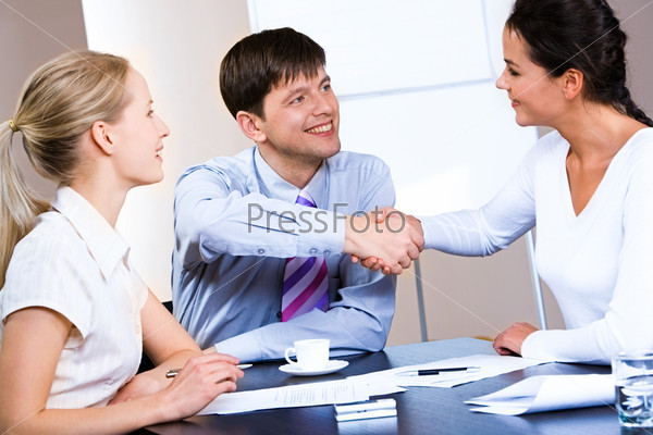 Portrait of woman and man concluding a bargain at business meeting