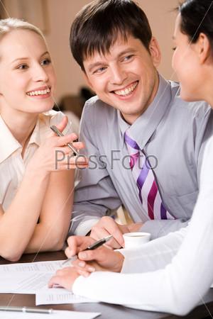 Портрет преуспевающих деловых людей, рассматривающих новый проект с улыбками