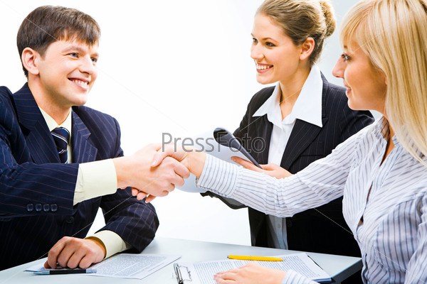 Business partners shaking hands and looking at each other at meeting