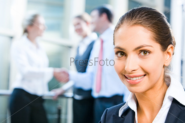 Image of pretty professional with charming smile on the background of people's handshake