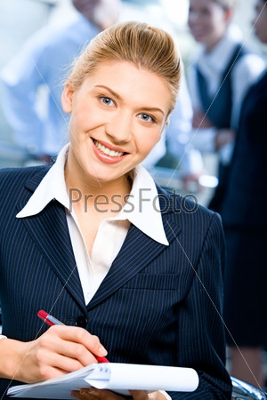 Portrait of strong secretary looking at camera during writing of text