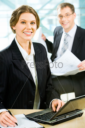 Confident business lady sitting at the table before a laptop