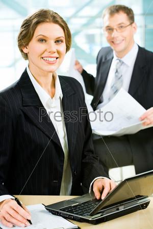 Деловая женщина сидит за столом перед ноутбуком