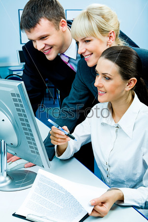 Businessteam of three smiling people looking at the monitor