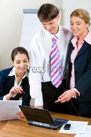 Трое деловых людей обсуждают важную компьютерную работу