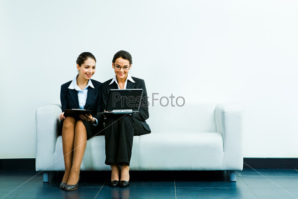 Portrait of business ladies sitting next to one another on the sofa