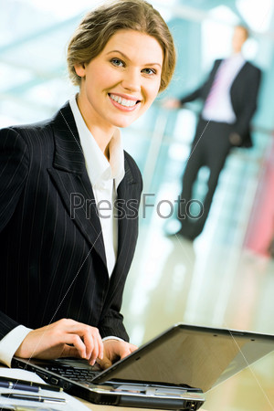 Portrait of smiling businesswoman sitting in the office and typing on the laptop