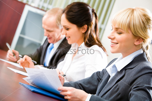 Image of confident students sitting at the desk looking at document