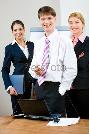 Group of three business people looking at camera and standing in the office
