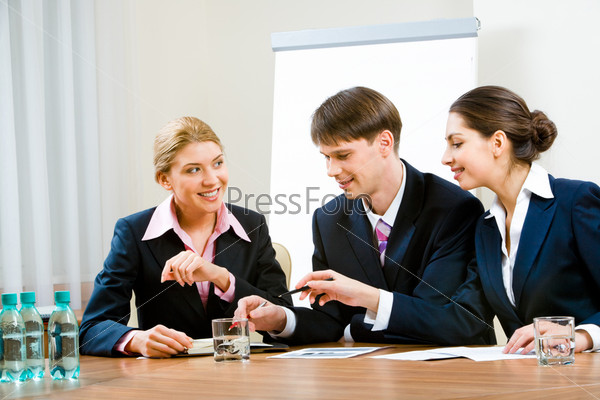 Portrait of three specialists discussing new ideas in the conference room