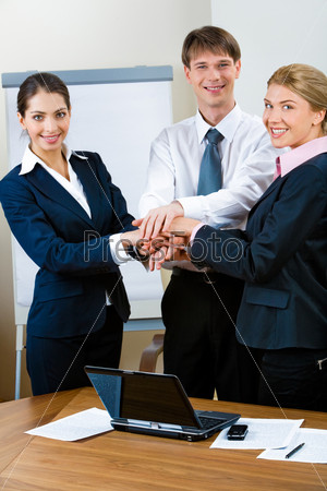 Image of three standing business partners making a pile with their hands