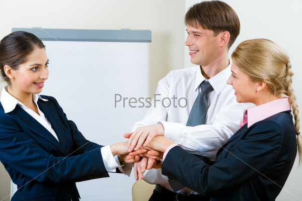 Portrait of three smiling business partners  looking at each other