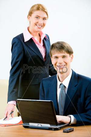 Image of business man and attractive secretary looking at camera